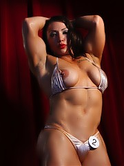 Sexy Brandi Mae is posing on stage flexing her powerful biceps and strong quads in a silver bikini, showing off her big, hard, pierced nipples.