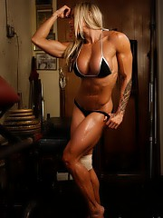 Even with a wrapped knee, tattooed female bodybuilder Larissa Reis is doing a tough workout in the gym, and posing in panties to show you how ripped she is and how good her muscular pecs, biceps, abs, glutes and abs look.