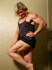 Mature female bodybuilder Clarkflex showing off the muscles in her pecs, big biceps, tight abs, muscular legs and glutes.